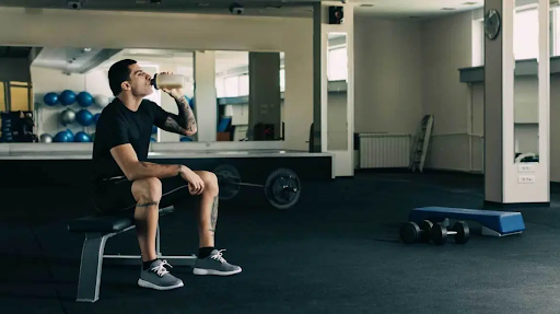 a man sitting in a gym after working out drinking a post workout shake
