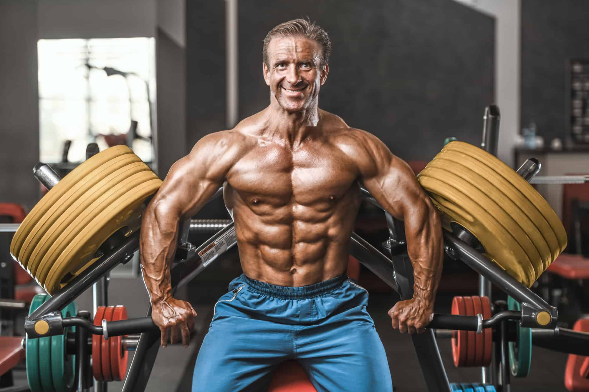 male body builder flexing in front of a workout machine with 45lb plates