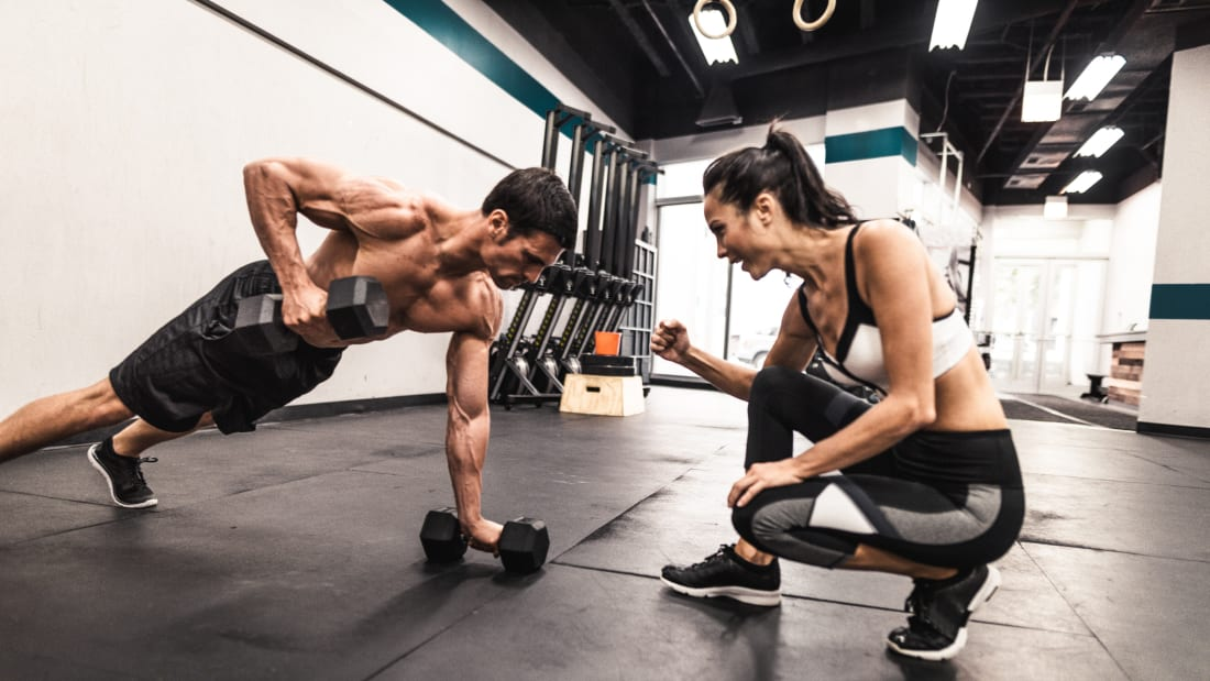 woman trainer encouraging male client doing dumbell pushups