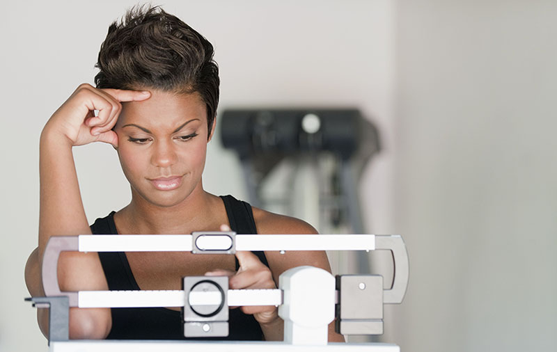 woman looking frustrated while checking her weight on a scale